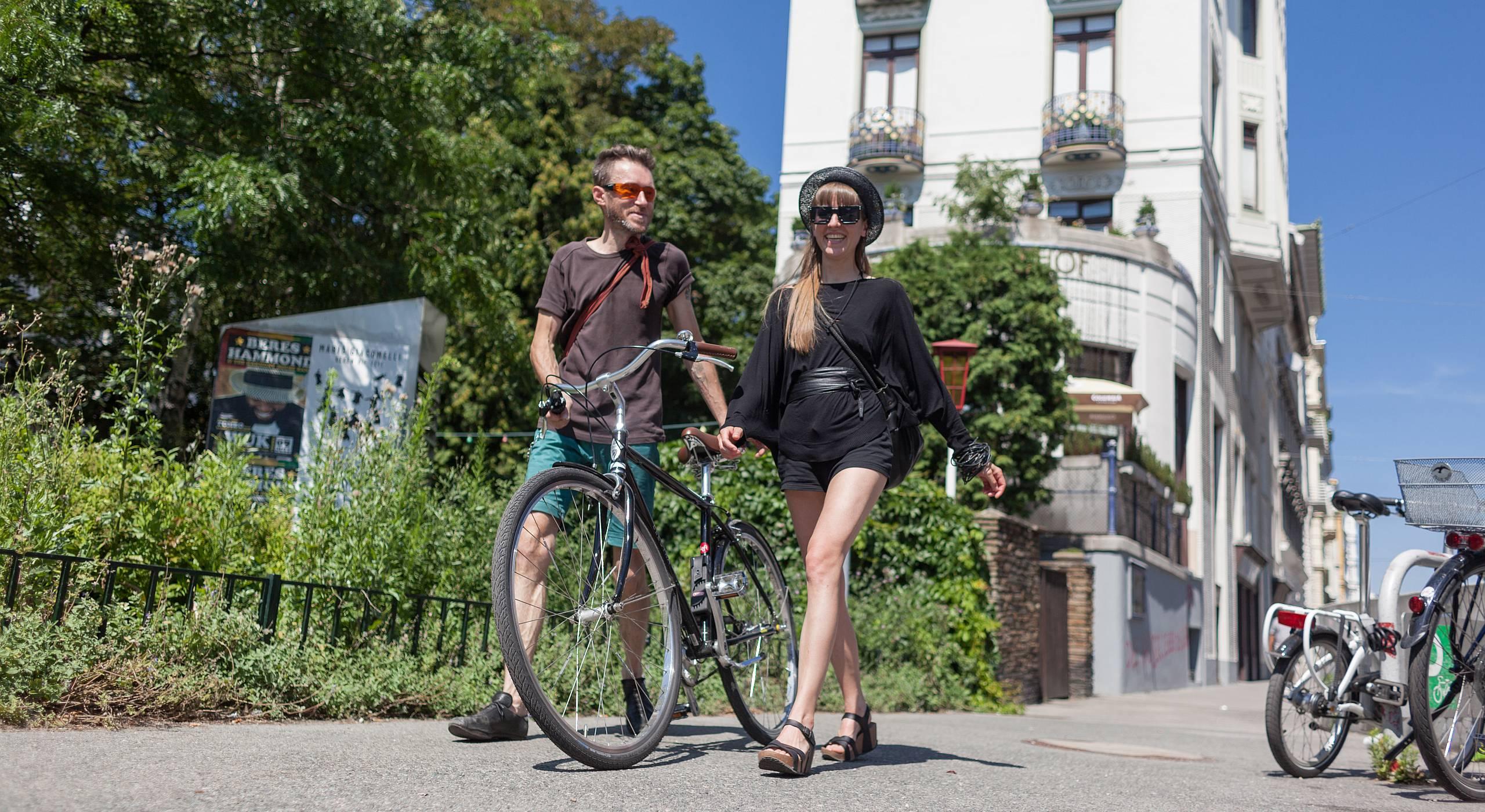 Ein junges Paar mit Fahrrad geht an einem sonnigen Tag in Wien spazieren. Foto von Stephan Doleschal