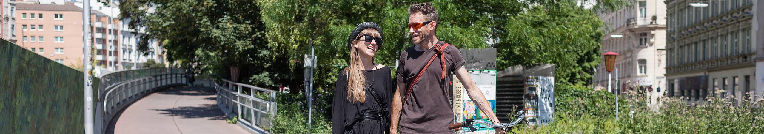 EIn junges Paar mit Fahrrad geht am Wientalradweg spazieren. Foto von Stephan Doleschal