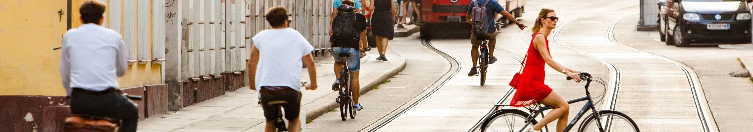 Mehrere Personen fahren mit Fahrrädern entlang der Straße, im Vordergrund eine alte Wiener Straßenbahn. Eine Frau in einem roten Sommerkleid auf einem Hollandrad quert die Fahrbahn. Foto von Peter Provaznik