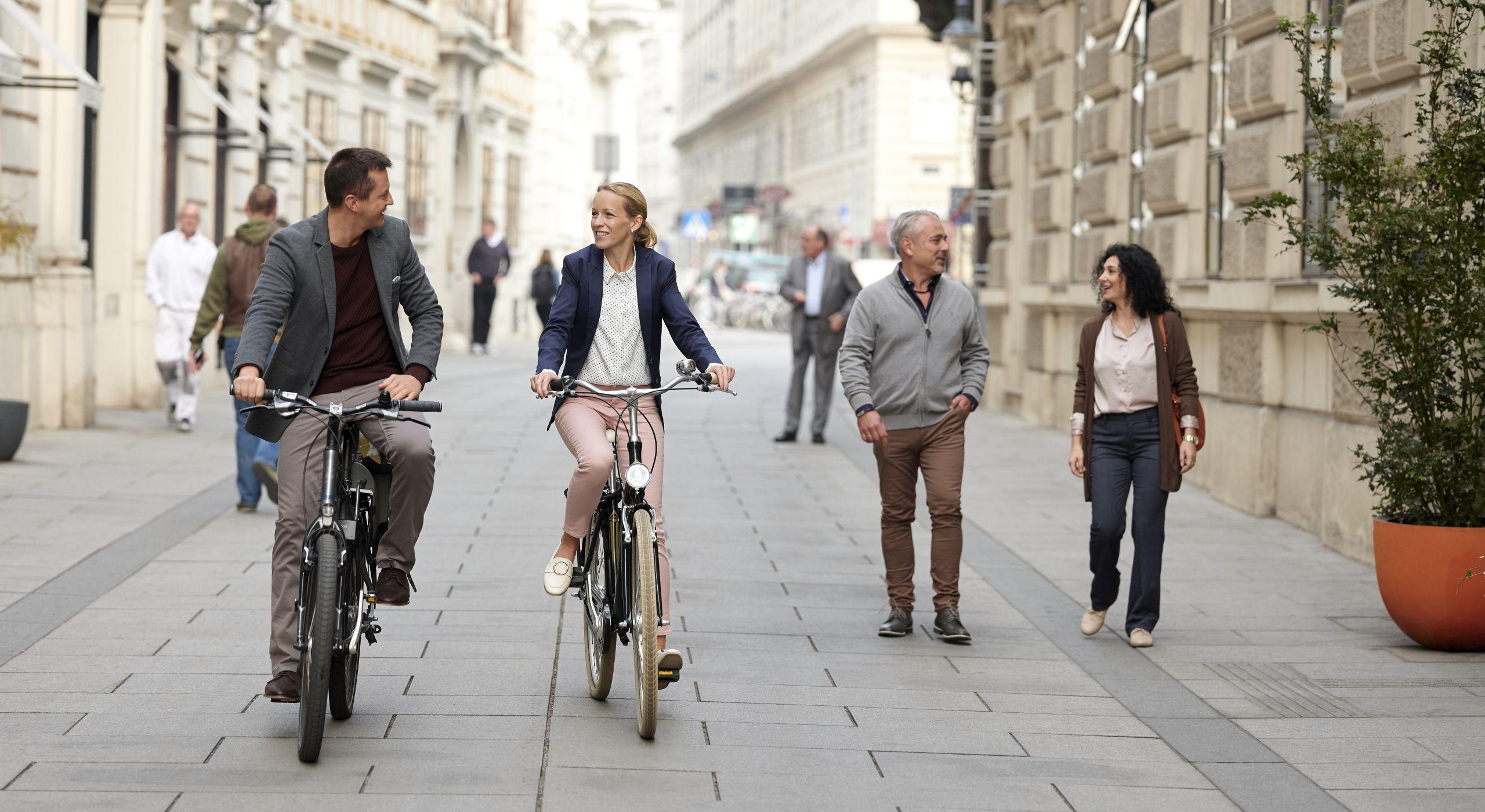 Zwei Personen, ein Mann und eine Frau, fahren mit dem Fahrrad und unterhalten sich. Im Hintergrund sieht man einen älteren Mann und eine Frau gehen. Auch sie unterhalten sich. Die Sizuation findet in einer gepflasterten Gasse in Wiens Innenstadt statt. Fotografiert von Ian Ehm.