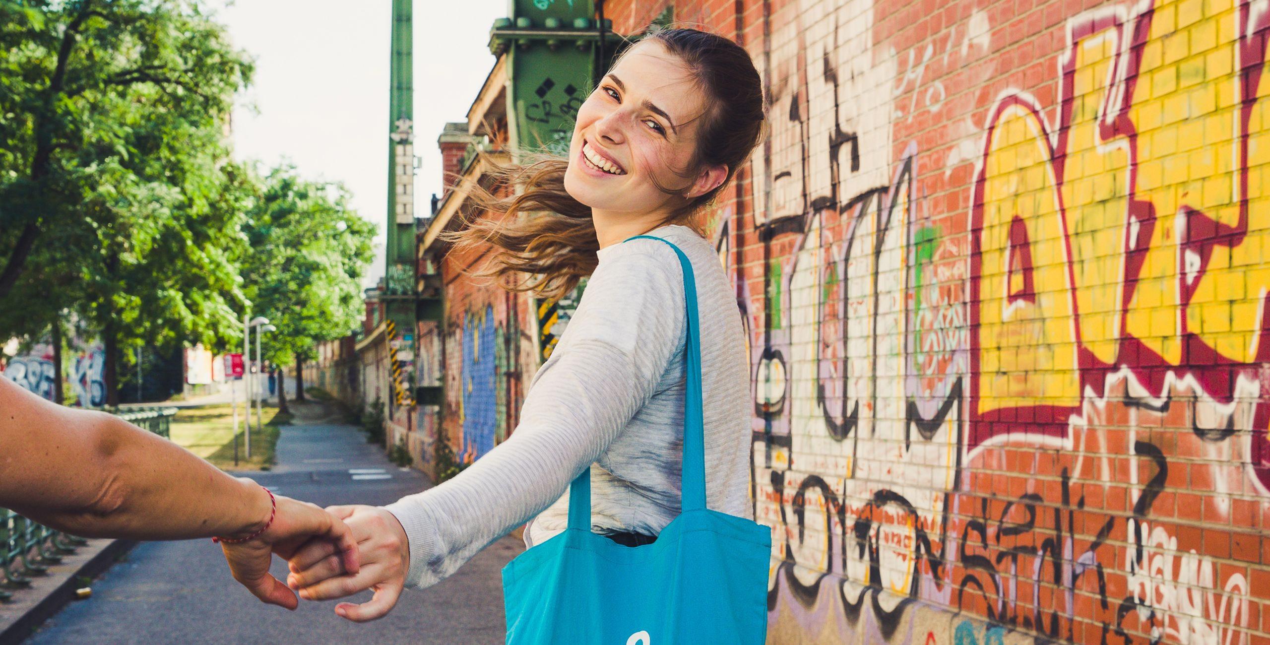 Junge Frau geht entlang einer bemalten Mauer und schaut nach hinten. Sie streckt die Hand aus. Foto: Heidi Pein