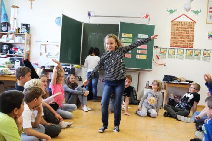 Mädchen stellt pantomimisch eine Mobilitätsform dar. Beim Workshop