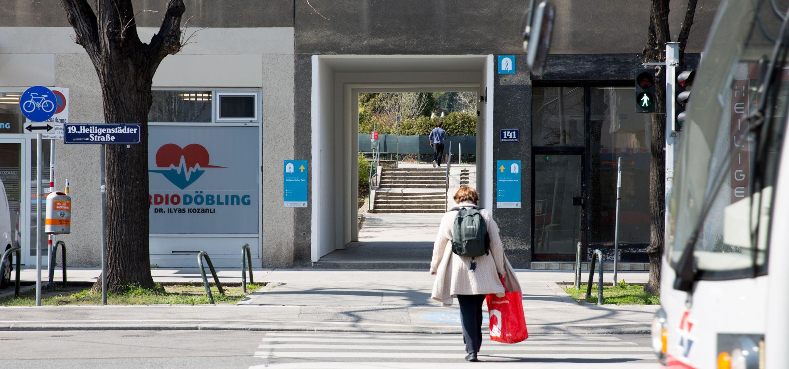 Mit blauen Schildern wird der Durchgang von der Heiligen Städter Straße 141 in die Kindergartengasse markiert.