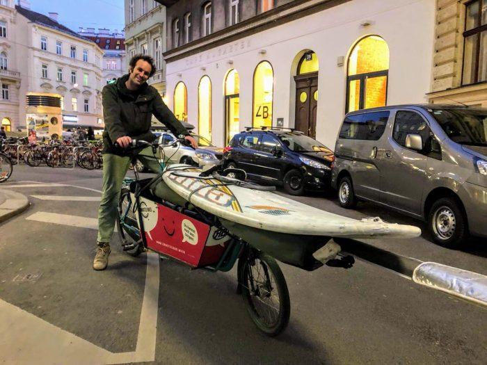 Mit einem Grätzlrad Transportfahrrad wird ein Surfbrett transportiert.
