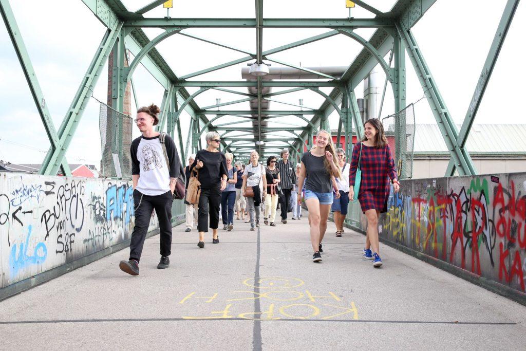 Eine Gruppe FußgängerInnen geht über die Brücke über den Westbahnhof.