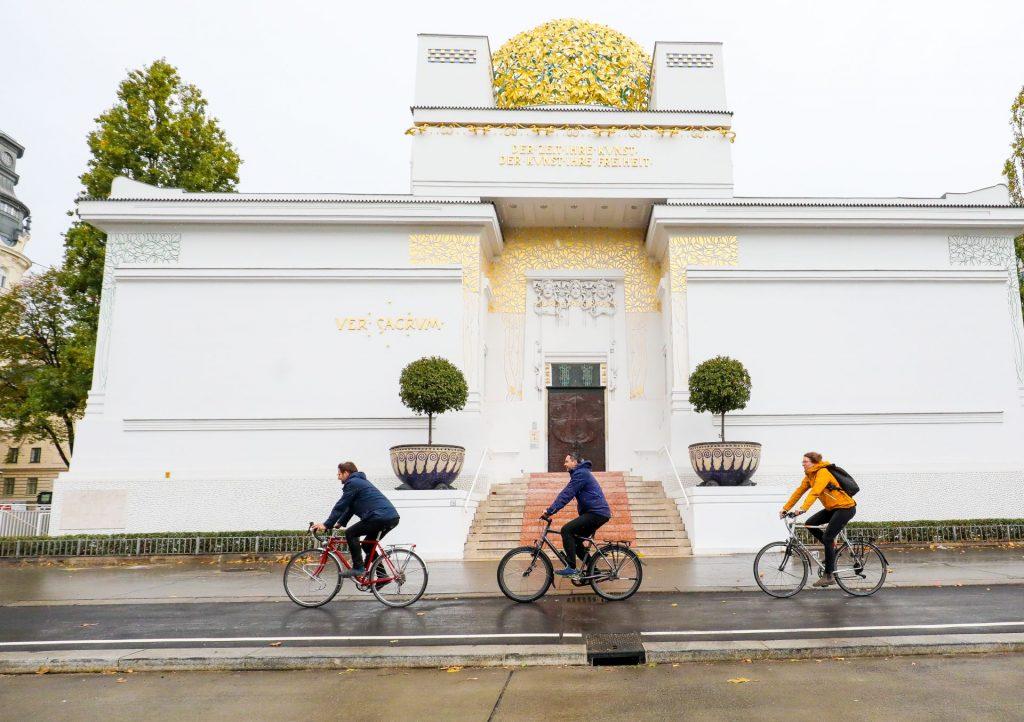 Drei Radfahrende radeln auf dem Radweg vor der Secession.